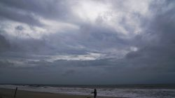 A man walks his dogs before Hurricane Florence comes ashore on Carolina Beach, North Carolina, U.S., September 13, 2018. REUTERS/Carlo Allegri
