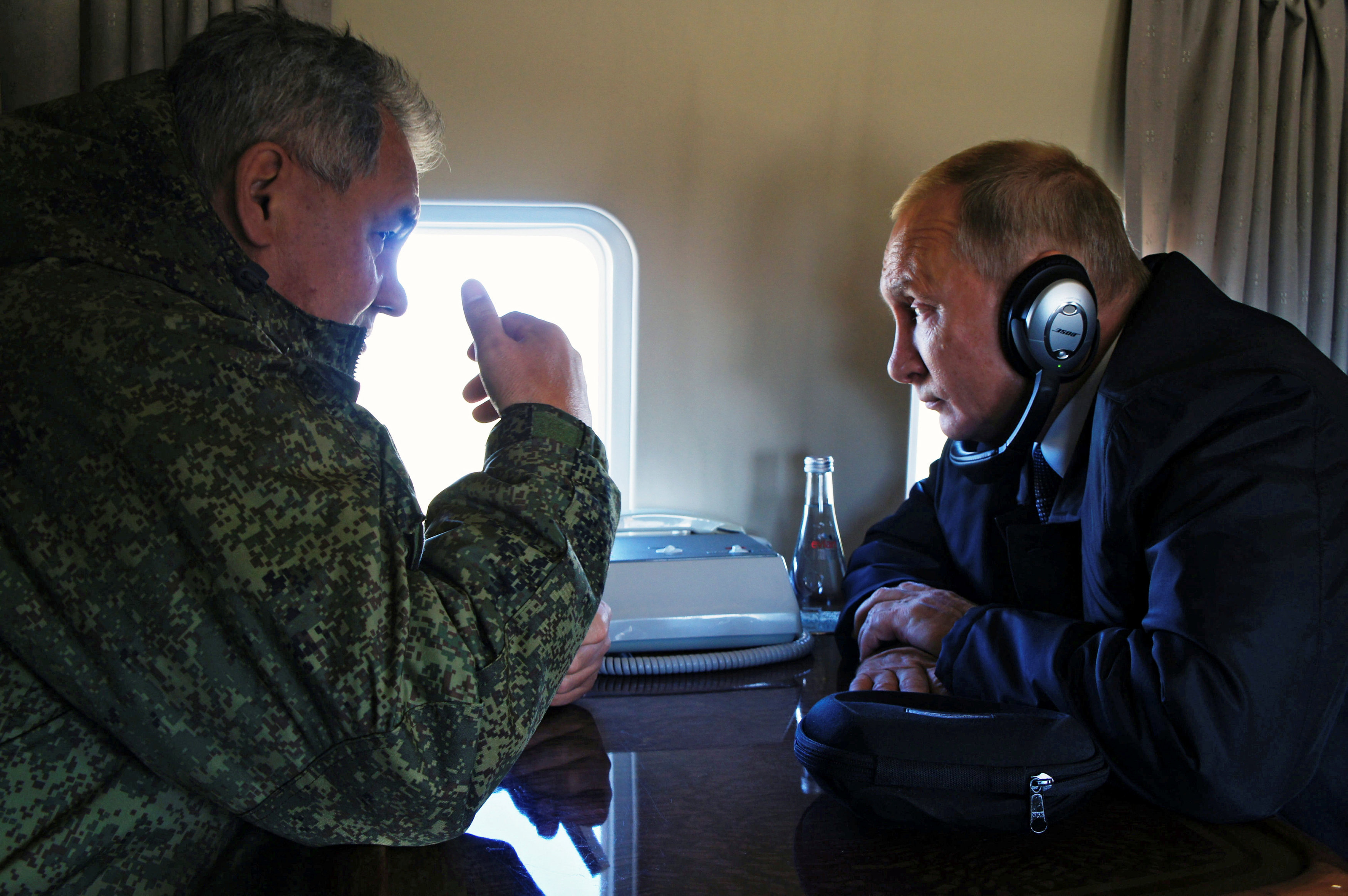 Russian President Vladimir Putin listens to Defence Minister Sergei Shoigu while flying over Tsugol training range in Zabaikalsky region, Russia, September 13, 2018. Sputnik/Alexei Nikolsky/Kremlin via REUTERS