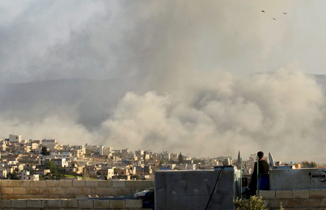 FILE PHOTO: A man watches as smoke rises after what activists said was an air strike on Atimah, Idlib province March 8, 2015. REUTERS/Ammar Abdullah/File Photo
