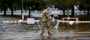 An Army member walks near the flooded Union Point Park Complex as the Hurricane Florence comes ashore in New Bern, North Carolina, U.S., September 13, 2018. REUTERS/Eduardo Munoz