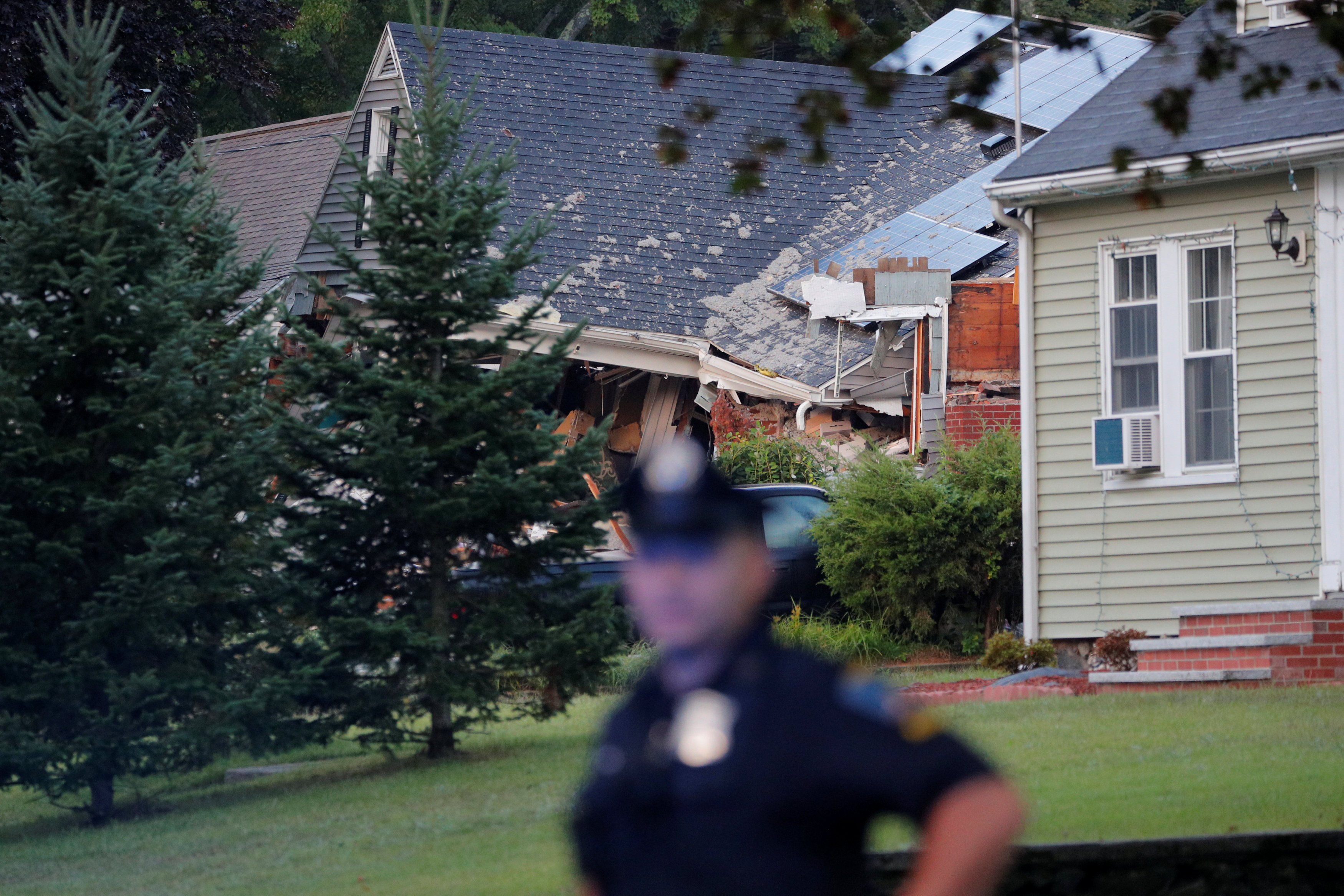 A police officer stands outside a home where a man died in a series of gas explosions in Lawrence, Massachusetts, U.S., September 14, 2018. REUTERS/Brian Snyder