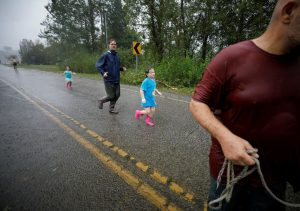 Ember Kelly (C), 5 years old, runs with Iva Williamson (2nd L), 4 years old, to a boat brought up to the edge of flood waters on a street in their neighborhood, during their rescue from rising flood waters in the aftermath of Hurricane Florence in Leland, North Carolina, U.S., September 16, 2018. REUTERS/Jonathan Drake