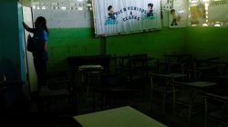 """A teacher stands next to a billboard that reads """"Welcome to classes"""" and empty desks in a classroom on the first day of school, in Caucagua, Venezuela September 17, 2018. REUTERS/Marco Bello"""