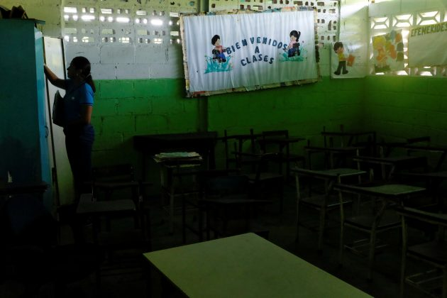 "A teacher stands next to a billboard that reads ""Welcome to classes"" and empty desks in a classroom on the first day of school, in Caucagua, Venezuela September 17, 2018. REUTERS/Marco Bello"