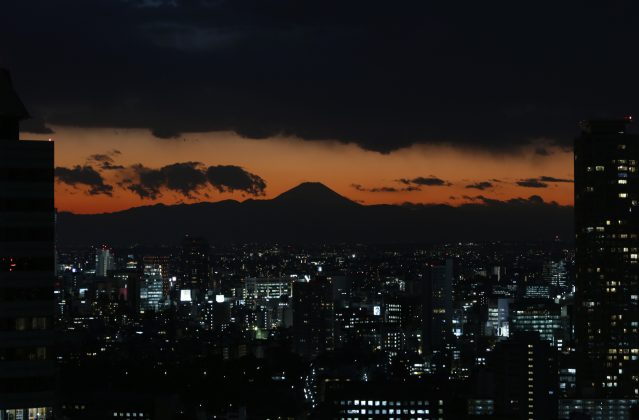 The silhouette of Japan's highest mountain Mount Fuji is seen beyond buildings in Tokyo in a file photo. REUTERS/Issei Kato
