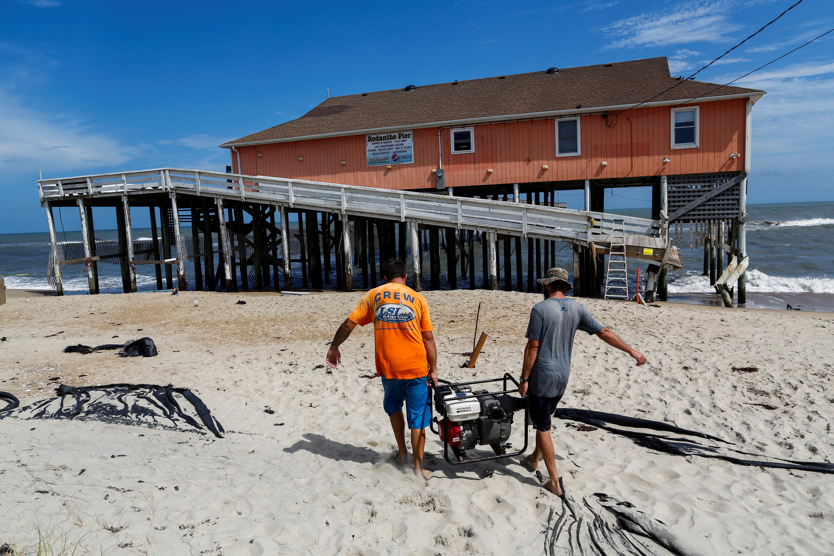 People work in the reconstruction of Rodanthe pier after being partially damaged after the pass of Hurricane Florence, now downgraded to a tropical depression in Rodanthe, North Carolina, U.S., September 18, 2018. REUTERS/Eduardo Munoz