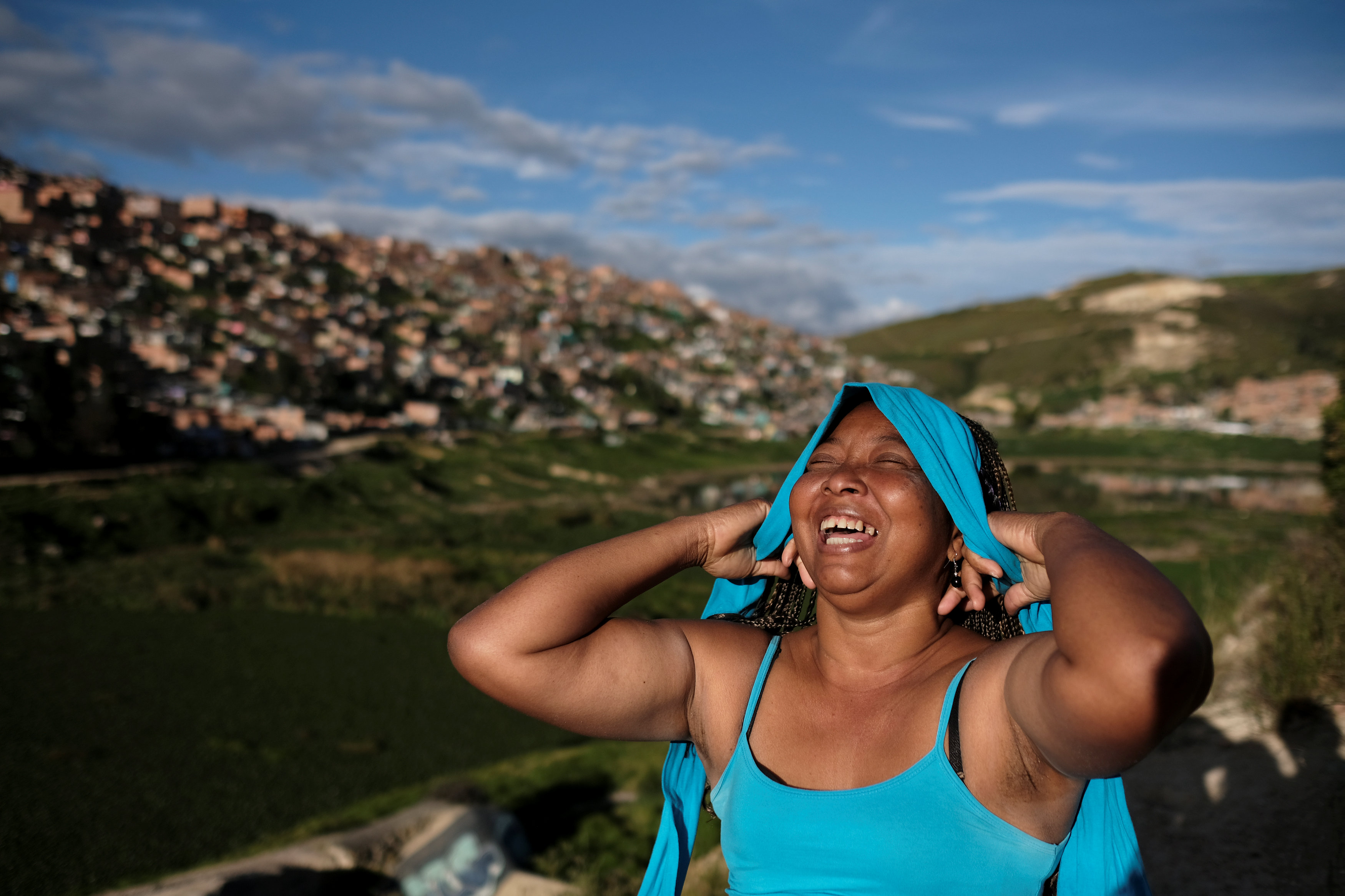 Lina, who said she was raped by dozens of right-wing paramilitary fighters in the Montes de Maria region during the five-decade civil war, laughs as she puts on a hairband in Soacha, on the outskirts of Bogota, Colombia, June 12, 2018. REUTERS/Nacho Doce