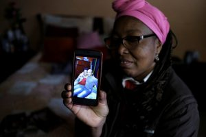Lina, who said she was raped by dozens of right-wing paramilitary fighters in the Montes de Maria region during the five-decade civil war, shows the picture of her son Over on the mobile phone inside her house in Soacha, on the outskirts of Bogota, Colombia, May 28, 2018. . REUTERS/Nacho Doce