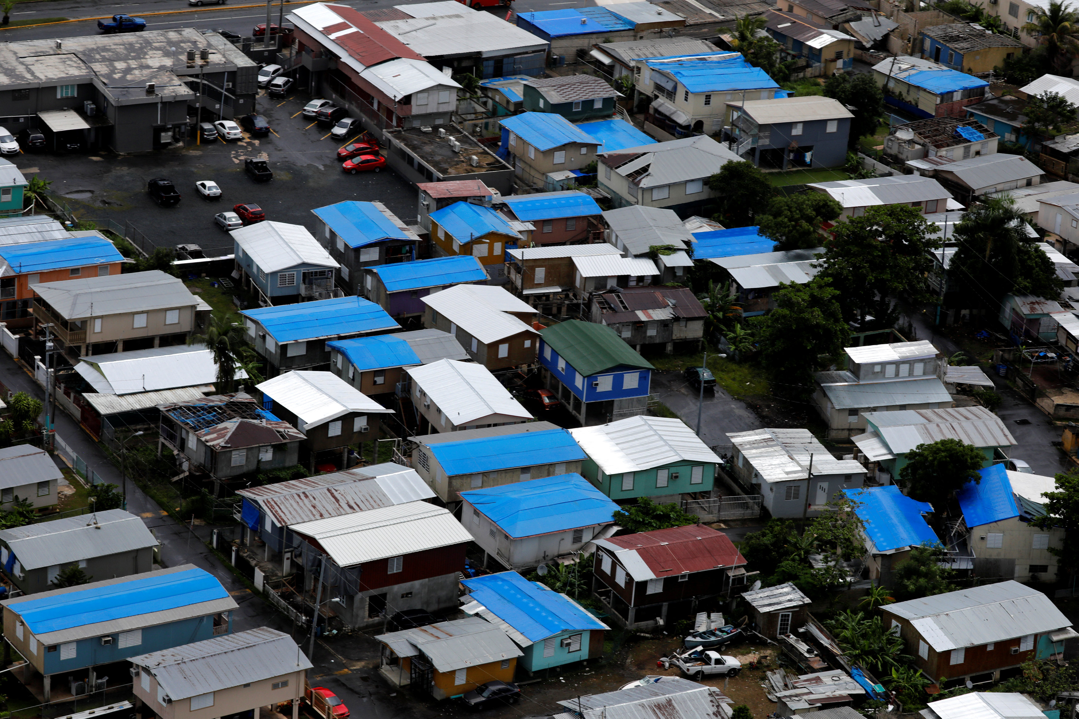 Plastic tarps over damaged roofs are seen on houses a year after Hurricane Maria devastated Puerto Rico in San Juan, Puerto Rico, September 18, 2018. Picture taken September 18, 2018. REUTERS/Carlos Barria