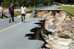 Local residents walk along the edge of a collapsed road that ran atop Patricia Lake's dam after it collapsed in the aftermath of Hurricane Florence, in Boiling Spring Lakes, North Carolina, U.S., September 19, 2018. REUTERS/Jonathan Drake