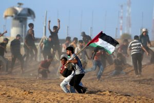 A wounded Palestinian is evacuated during a protest calling for lifting the Israeli blockade on Gaza and demanding the right to return to their homeland, at the Israel-Gaza border fence, in the southern Gaza Strip September 21, 2018. REUTERS/Ibraheem Abu Mustafa