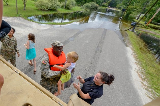 U.S. Army Pfc. Marlen Squire, of the South Carolina National Guard, assists in evacuating local residents from floodwaters as a result of Hurricane Florence in Dongola, South Carolina, U.S. September 24, 2018. Staff Sgt. Jorge Intriago/U.S. Army National Guard/Handout via REUTERS