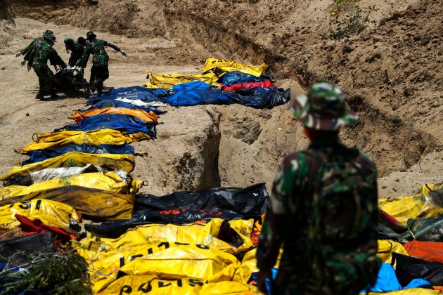 Soldiers move dead bodies of the victims of the earthquake and tsunami during a mass burial at the Poboya Cemetery in Palu, Central Sulawesi, Indonesia, October 2, 2018. REUTERS/Athit Perawongmetha