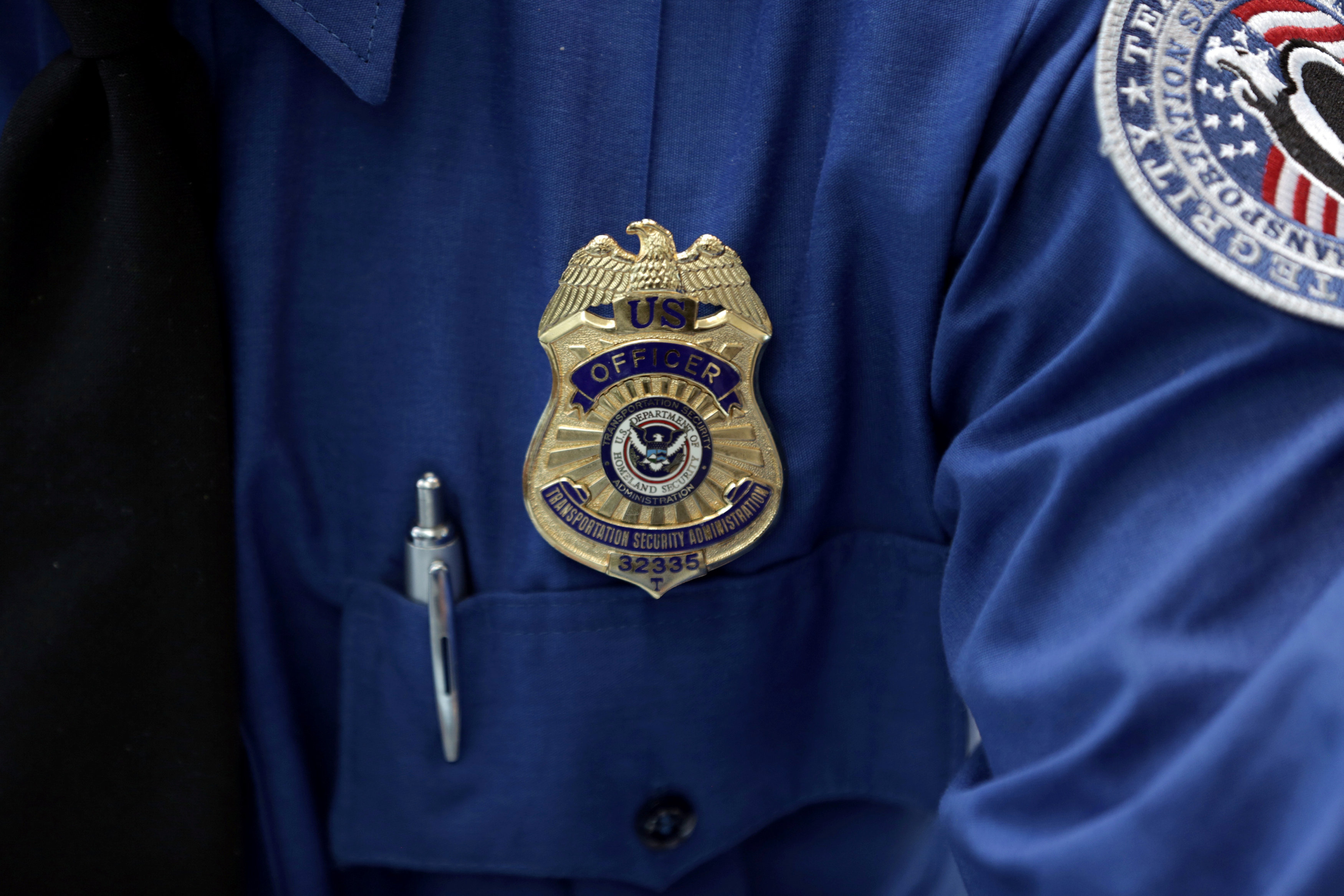 FILE PHOTO: A Transportation Security Administration (TSA) official wears a TSA badge at Terminal 4 of JFK airport in New York City, U.S., May 17, 2017. REUTERS/Joe Penney/File Photo