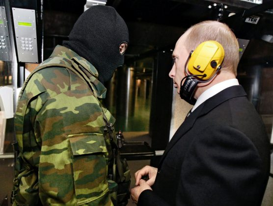 FILE PHOTO: Russian President Vladimir Putin and a masked security officer stand at a shooting gallery of the new GRU military intelligence headquarters building as he visits it in Moscow, Russia November 8, 2006.REUTERS/ITAR-TASS/PRESIDENTIAL PRESS SERVICE/File Photo