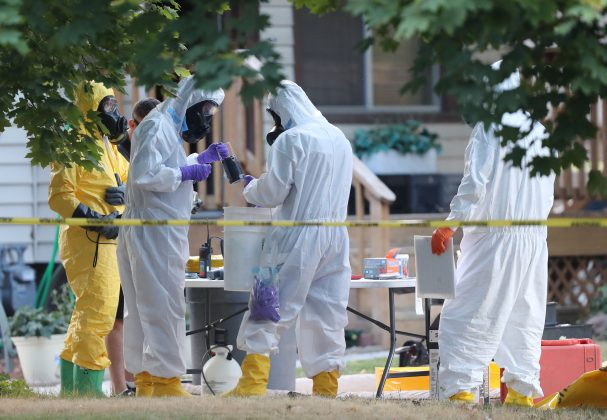 """FBI and law enforcement officers in hazmat suites prepare to enter a house, which FBI says was investigating """"potentially hazardous chemicals"""" in Logan, Utah, U.S., October 3, 2018. REUTERS/George Frey"""