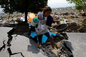 A girl carries valuables from the ruins of her house after an earthquake hit the Balaroa sub-district in Palu, Indonesia, October 4, 2018. REUTERS/Beawiharta