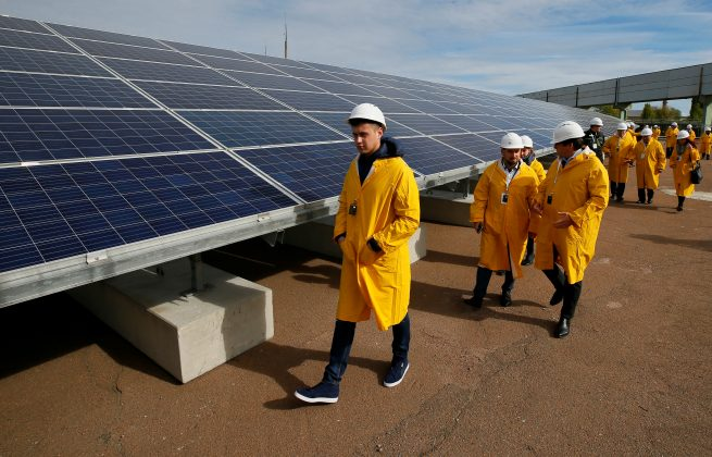 Visitors walk past solar panels at a solar power plant built on the site of the world's worst nuclear disaster, Chernobyl, Ukraine October 5, 2015. REUTERS/Gleb Garanich