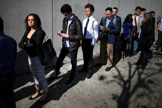 FILE PHOTO: People wait in line to attend TechFair LA, a technology job fair, in Los Angeles, California, U.S., January 26, 2017. REUTERS/Lucy Nicholson - RC1458E83C90