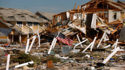 An American flag flies amongst rubble left in the aftermath of Hurricane Michael in Mexico Beach, Florida, U.S. October 11, 2018. REUTERS/Jonathan Bachman