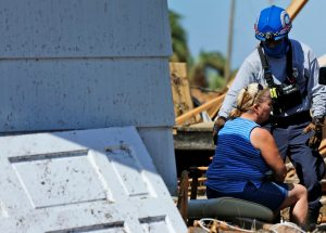 Bianna Kelsay is consoled by member of rescue personnel after being saved from her business damaged by Hurricane Michael in Mexico Beach, Florida, U.S. October 11, 2018. REUTERS/Jonathan Bachman