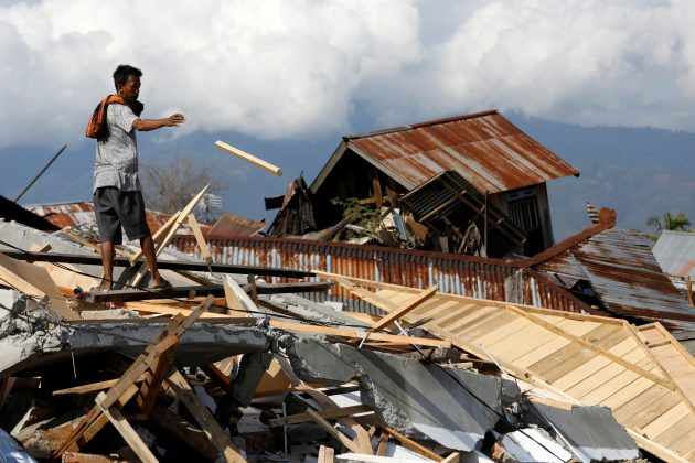 A man salvages wood from the ruins of a house in the Petobo neighbourhood which was hit by an earthquake and liquefaction in Palu, Central Sulawesi, Indonesia October 10, 2018. REUTERS/Darren Whiteside
