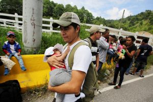 A man carries a baby as he walks with other Hondurans fleeing poverty and violence as they move in a caravan toward the United States, in the west side of Honduras October 14, 2018. REUTERS/ Jorge Cabrera