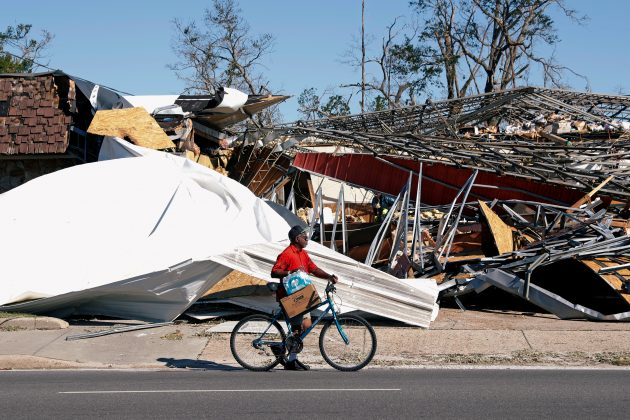 A man carries food and water past a building damaged by Hurricane Michael in Parker, Florida, U.S., October 13, 2018. REUTERS/Terray Sylvester