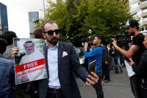 A man holds a picture of Saudi journalist Jamal Khashoggi as media members film during a protest outside the Saudi Consulate in Istanbul, Turkey October 8, 2018. REUTERS/Murad Sezer