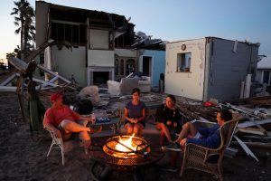A family sits by a fire and prepares to eat a dinner of MREs in front of their house with no roof following Hurricane Michael in Mexico Beach, October 13. REUTERS/Carlo Allegri