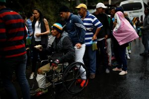 FILE PHOTO: Undocumented Venezuelans migrants stand in line to wait for food to be handed out by a group of Colombians, who fund an informal soup kitchen, outside a makeshift shelter in Pamplona, Colombia August 26, 2018. REUTERS/Carlos Garcia Rawlins