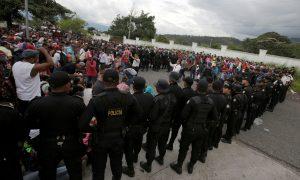 Guatemalan police officers watch as Honduran migrants, part of a caravan trying to reach the U.S., arrive in Esquipulas city in Guatemala, October 15, 2018. REUTERS/Jorge Cabrera