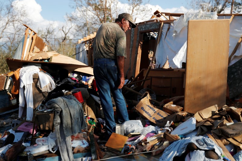 Bernard Sutton, 64, picks through the remains of his home destroyed by Hurricane Michael in Fountain, Florida, U.S., October 15, 2018. REUTERS/Terray Sylvester