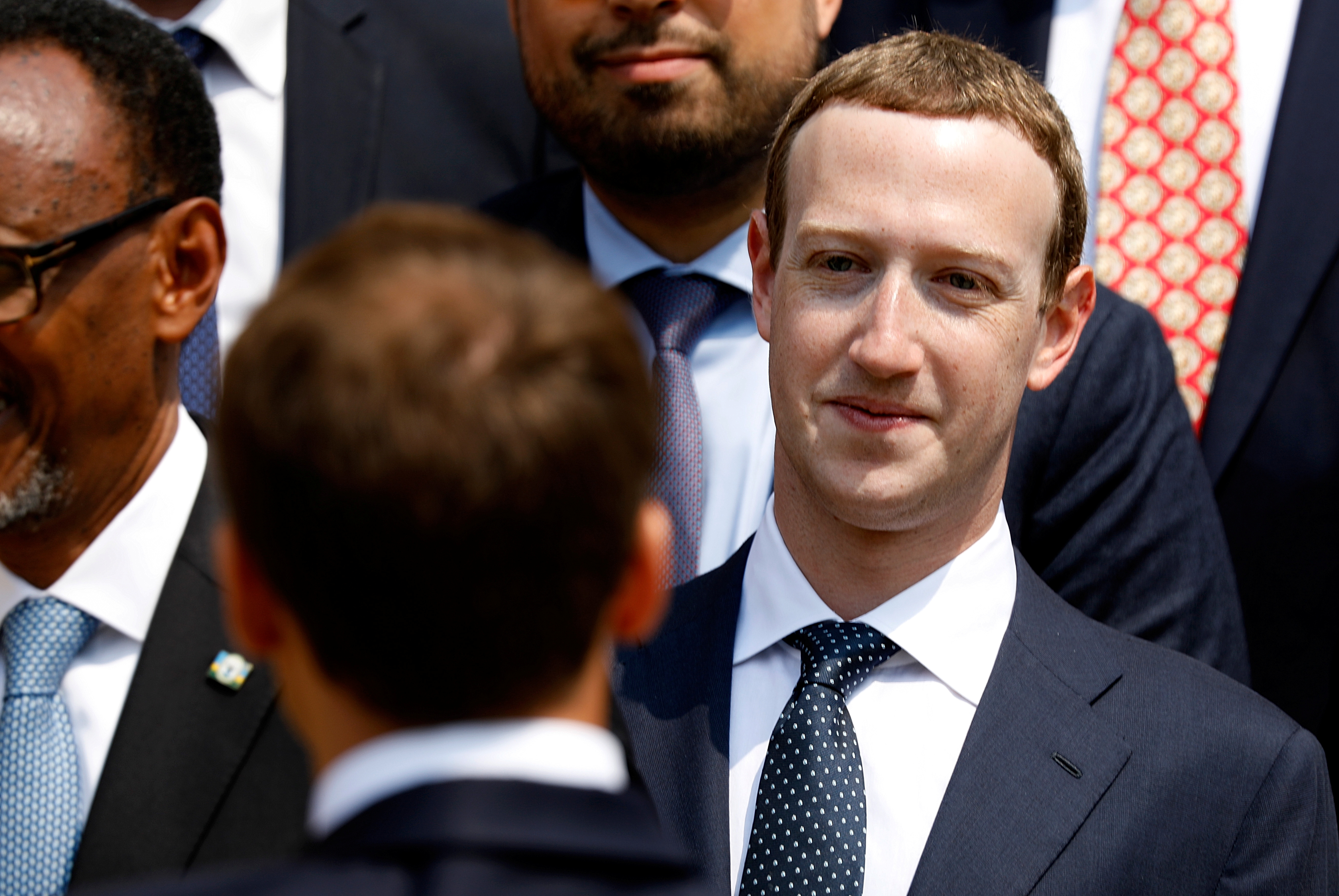 """Facebook's CEO Mark Zuckerberg listens to French President Emmanuel Macron after a family picture with guests of the """"Tech for Good Summit"""" at the Elysee Palace in Paris, France, May 23, 2018. REUTERS/Charles Platiau/Pool"""