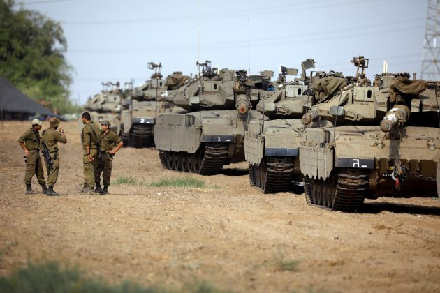 Israeli soldiers speak next to tanks as military armoured vehicles gather in an open area near Israel's border with the Gaza Strip October 18, 2018. REUTERS/Amir Cohen