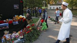 People place flowers and candles at a makeshift memorial near the scene of a recent attack on a local college in the city of Kerch, Crimea October 18, 2018. REUTERS/Pavel Rebrov