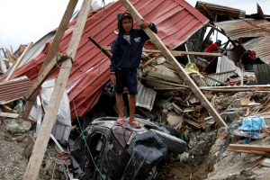 Ikhmal Yudanto, 15, stands on his mother's car at his destroyed house hit by an earthquake, in Balaroa neighbourhood, Palu, Central Sulawesi, Indonesia, October 11, 2018. REUTERS/Jorge Silva
