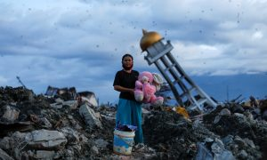 A woman holds a stuffed rabbit toy after it was found at her destroyed house where she said she had lost her three children after the area was hit by an earthquake, in Palu, Central Sulawesi, Indonesia, October 7, 2018. REUTERS/Jorge Silva/File photo