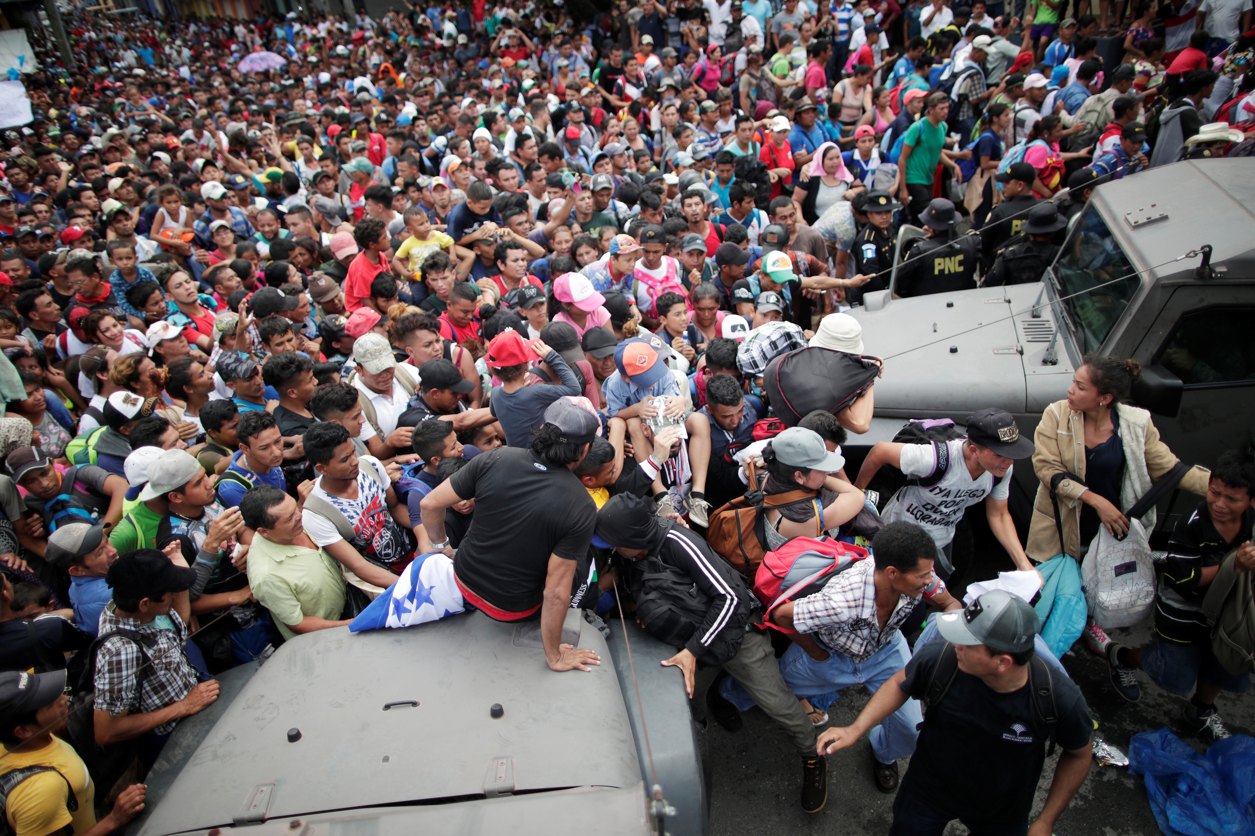 Honduran migrants, part of a caravan trying to reach the U.S., storm a border checkpoint to cross into Mexico, in Tecun Uman, Guatemala October 19, 2018. REUTERS/Ueslei Marcelino