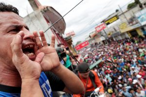 A Honduran migrant, part of a caravan trying to reach the U.S., yells as others wait to cross into Mexico, in Tecun Uman, Guatemala October 19, 2018. REUTERS/Ueslei Marcelino