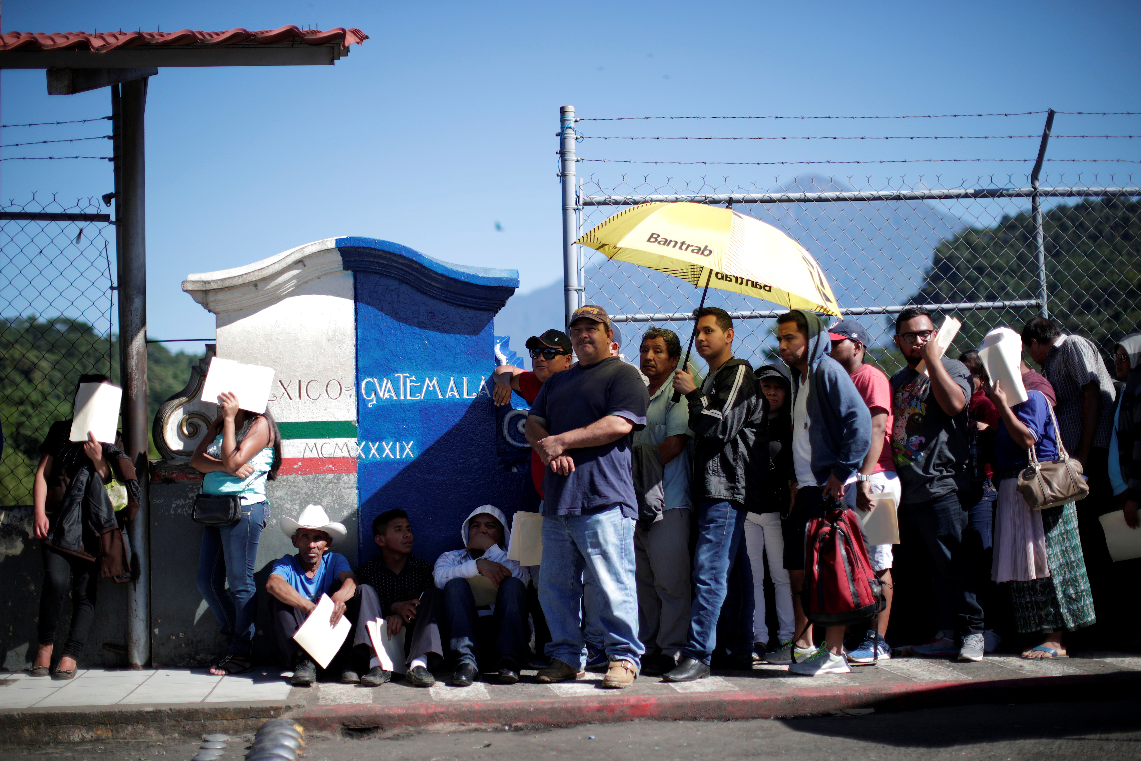 Central American migrants queue at a border connecting Guatemala and Mexico while waiting to cross into Mexico, in Talisman, Mexico October 23, 2018. REUTERS/Ueslei Marcelino