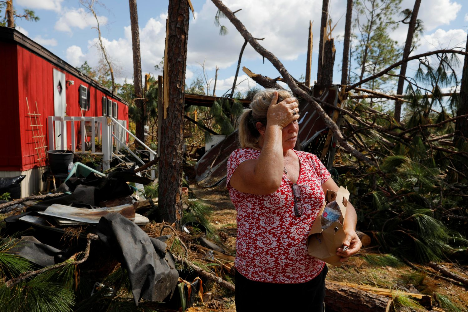 Hurricane Michael survivor Yvette Beasley stands in her front yard during a wellbeing check by a 50 Star Search and Rescue team in Fountain, Florida, U.S., October 17, 2018. REUTERS/Brian Snyder