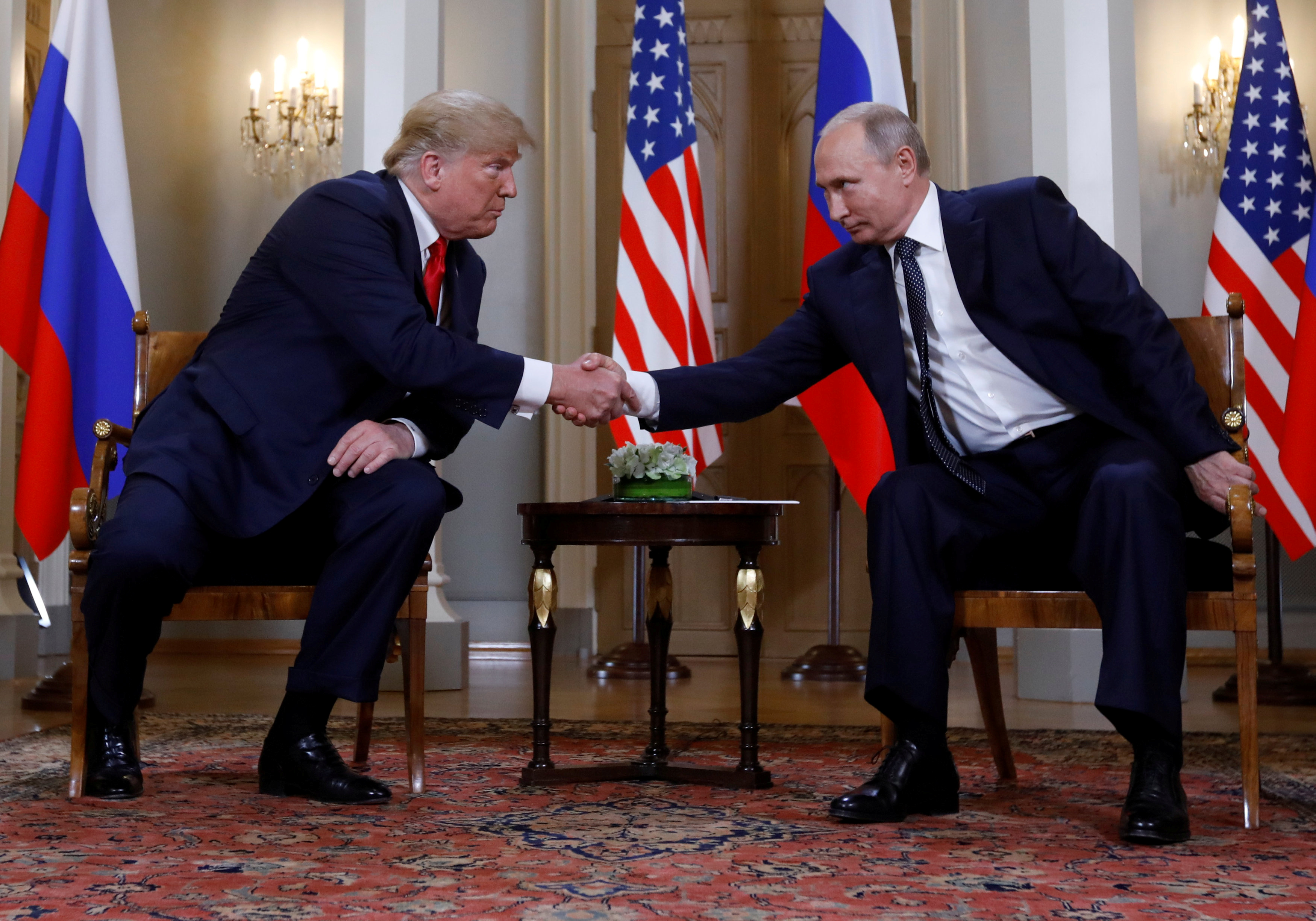 FILE PHOTO: U.S. President Donald Trump and Russia's President Vladimir Putin shake hands as they meet in Helsinki, Finland July 16, 2018. REUTERS/Kevin Lamarque