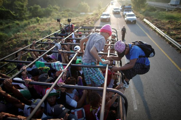 Migrants, part of a caravan of thousands from Central America en route to the United States, hitchhike on a truck along the highway to Arriaga from Pijijiapan, Mexico, October 26, 2018. REUTERS/Ueslei Marcelino