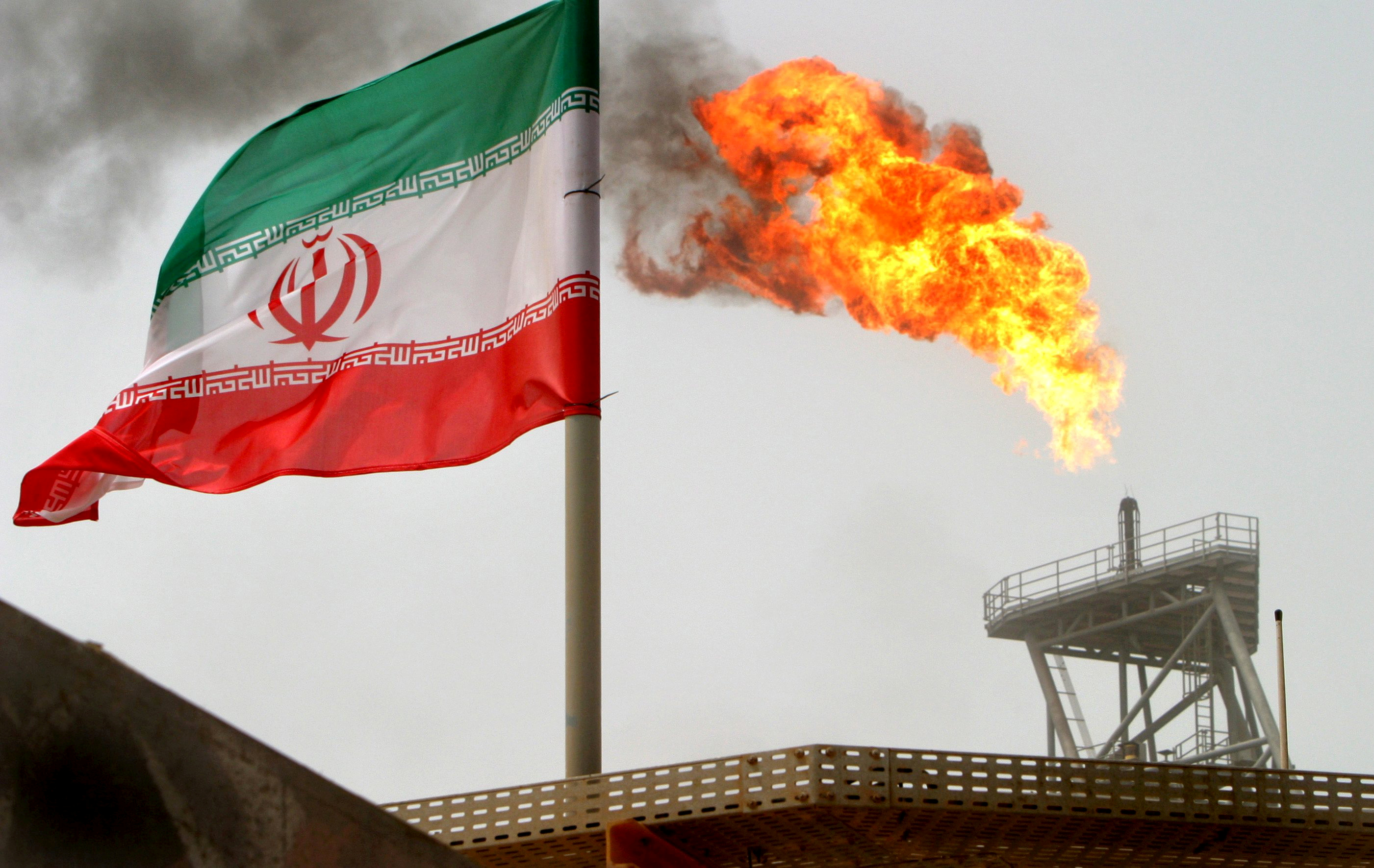 FILE PHOTO: gas flare on an oil production platform in the Soroush oil fields is seen alongside an Iranian flag in the Gulf July 25, 2005. REUTERS/Raheb Homavandi/File Photo