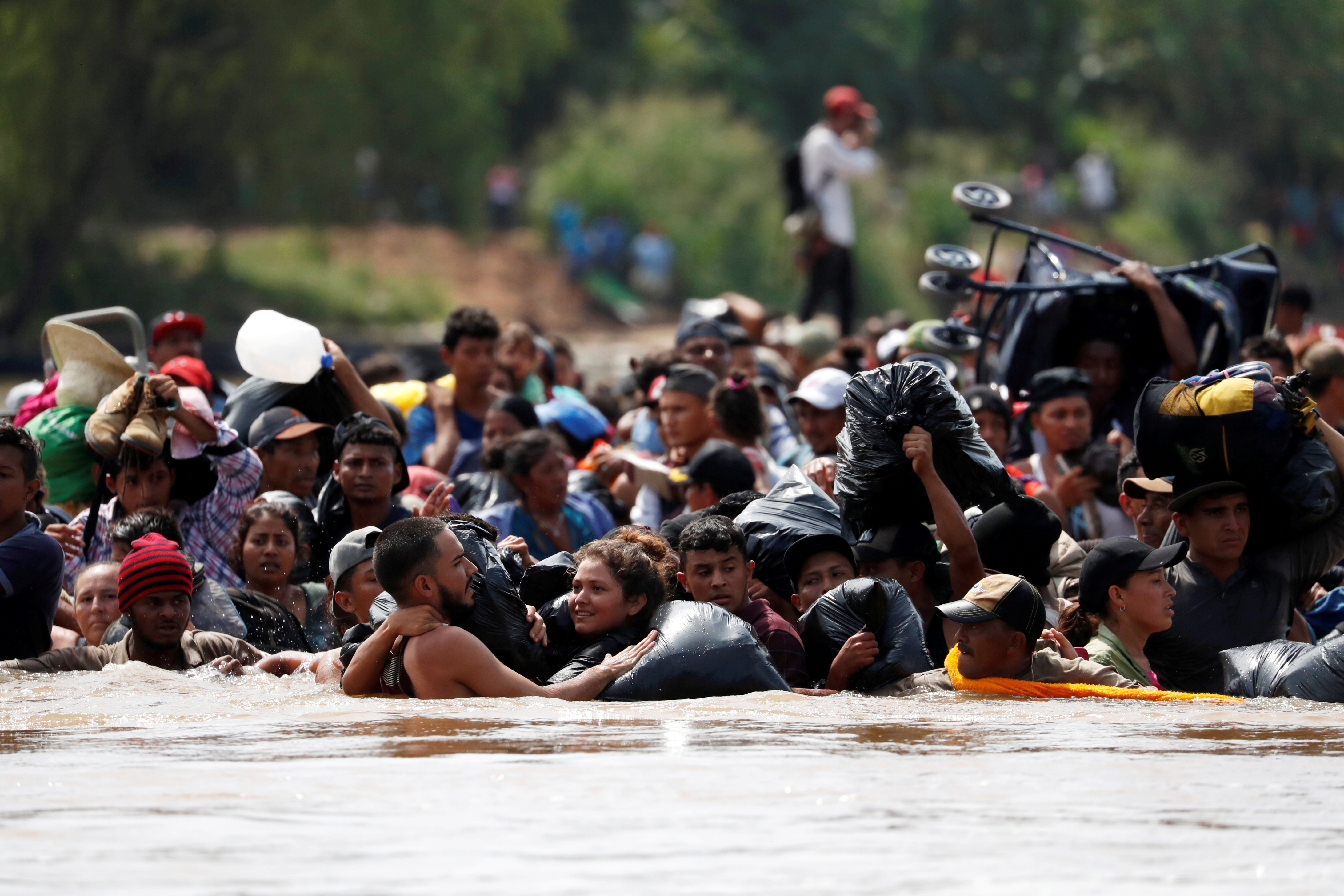 Central American migrants walk through the Suchiate river, the natural border between Guatemala and Mexico, in their bid to reach the U.S., as seen from Tecun Uman, Guatemala October 29, 2018. REUTERS/Carlos Garcia Rawlins