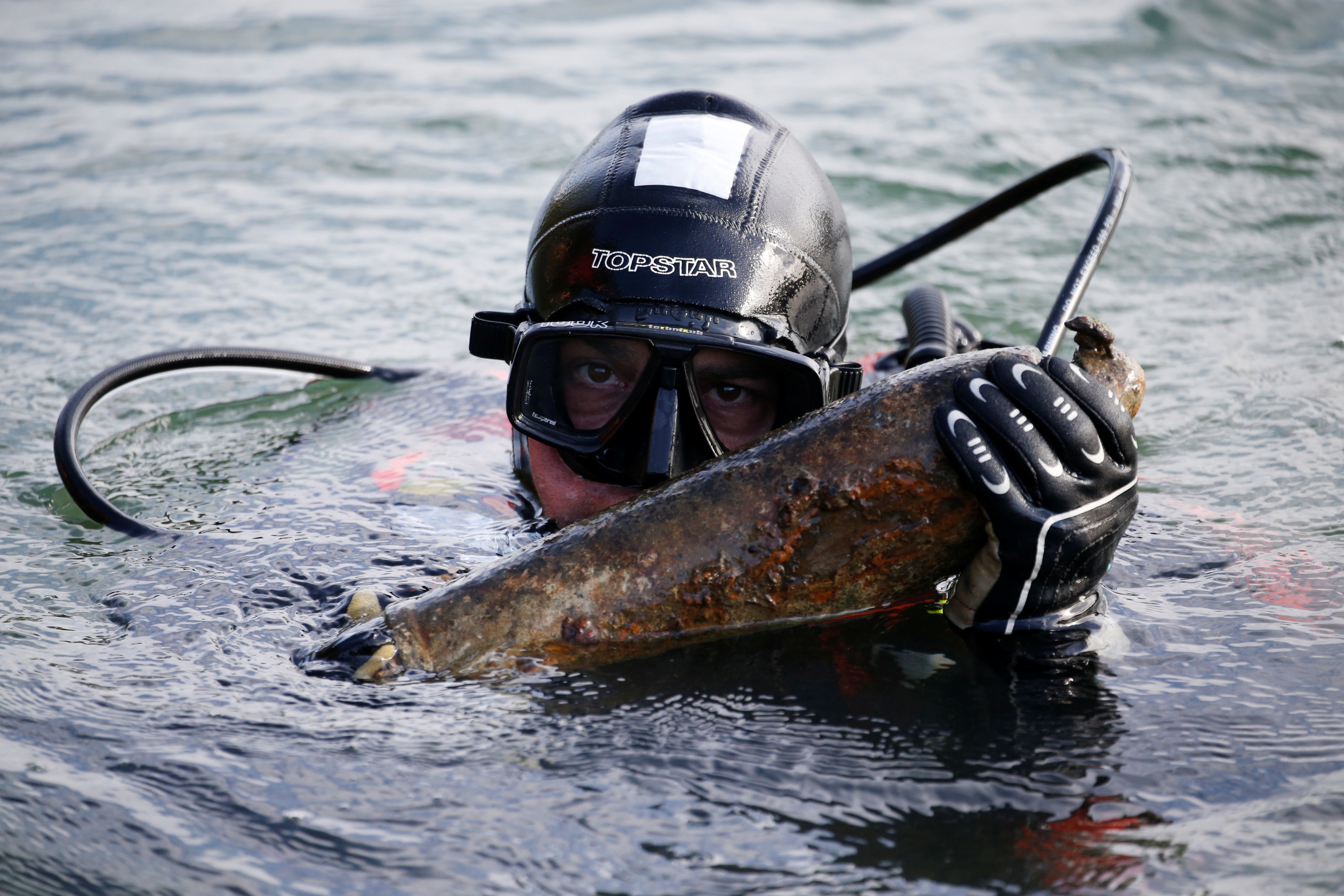 A diver from a bomb-disposal unit gies up the surface an unexploded shell recovered in the Meuse River at Sivry-sur-Meuse, close to WWI battlefields, near Verdun, France, October 23, 2018 before the centenial commemoration of the First World War Armistice Day. REUTERS/Pascal Rossignol