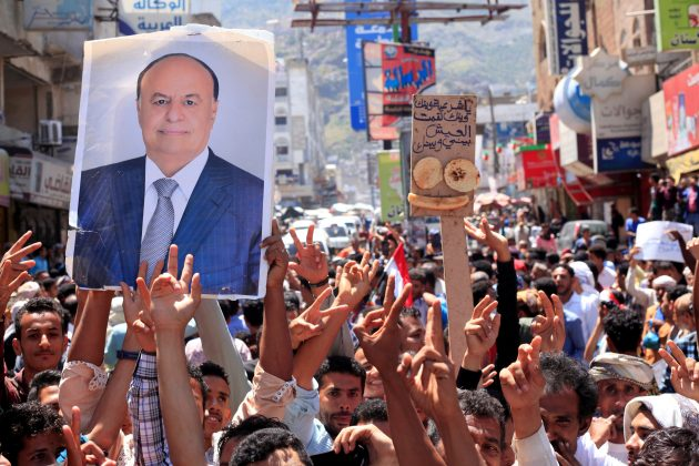 FILE PHOTO: Protesters hold up a poster of Yemeni President Abd-Rabbu Mansour Hadi during a protest against the deteriorating economy in Taiz, Yemen, October 4, 2018. REUTERS/Anees Mahyoub/File Photo