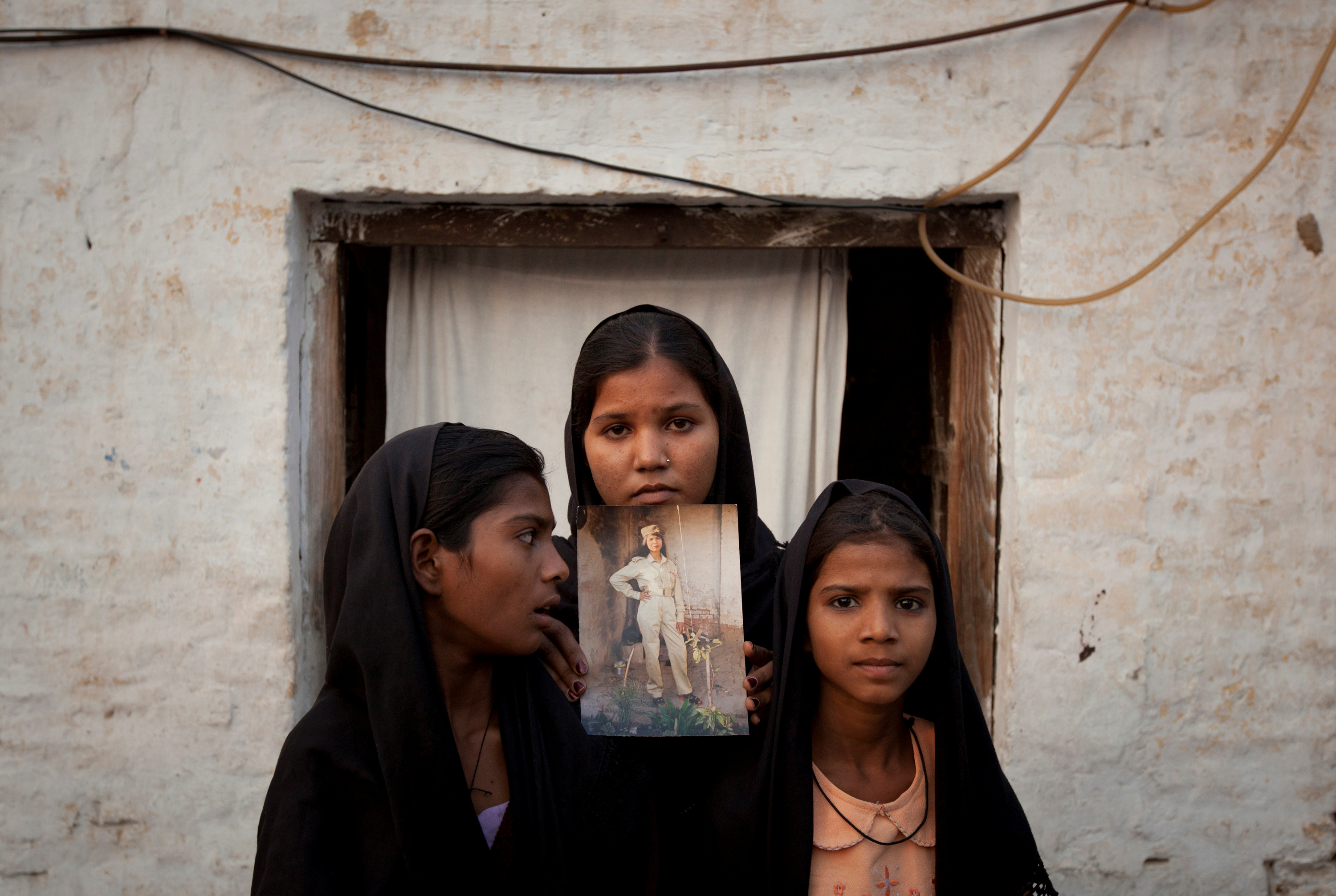 FILE PHOTO: The daughters of Pakistani Christian woman Asia Bibi pose with an image of their mother while standing outside their residence in Sheikhupura located in Pakistan's Punjab Province November 13, 2010. REUTERS/Adrees Latif/File Photo