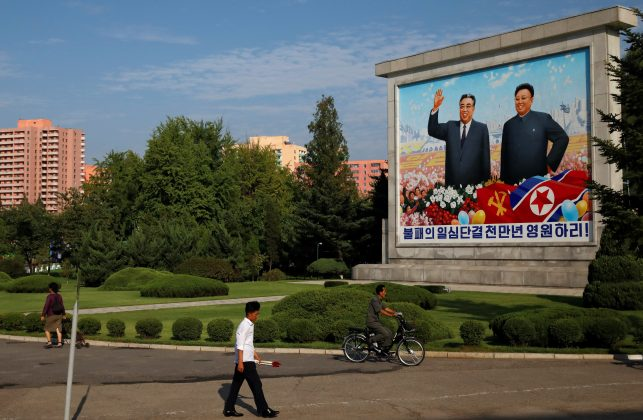 FILE PHOTO: Residents pass by a painting of late North Korean leaders Kim Il Sung and Kim Jong Il in Pyongyang, North Korea, September 6, 2018. REUTERS/Danish Siddiqui
